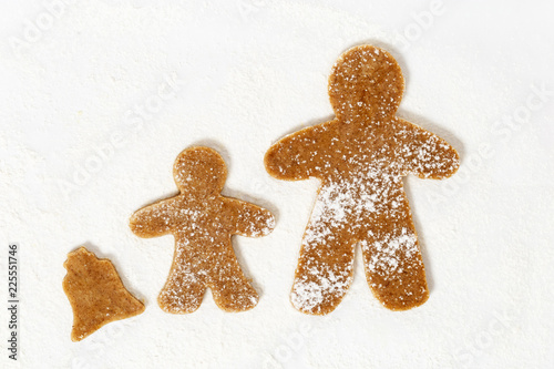 Tuinposter Koekjes Biscuits strewed with flour. Cookies in form of Gingerbread man on paper for baking. Raw Gingerbread Cookie.