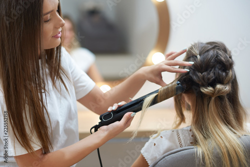 Hairdresser making curls with using straightener in beauty salon
