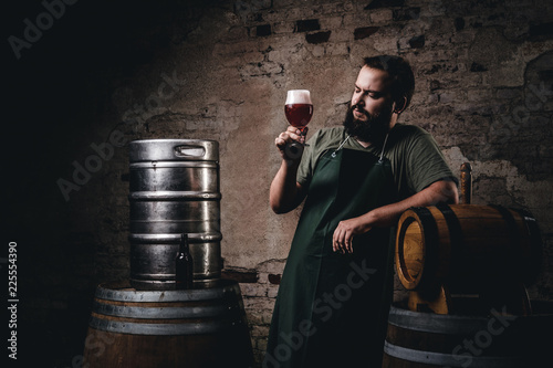 Foto Brewer in apron standing near barrels and drinks craft beer at old brewery factory