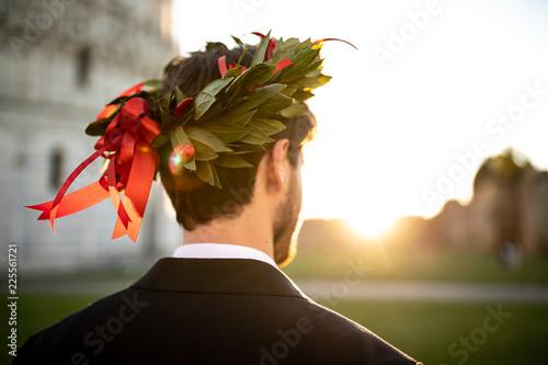 Photographie Giovane ragazzo laureato con corona d'alloro in testa e vestito elegante visto di spalle