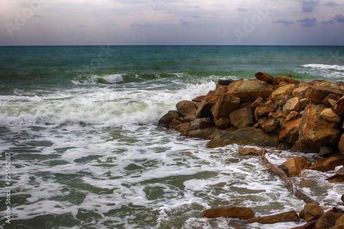Sea storm, waves breaking on a rock breakwater.