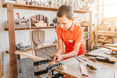 Fototapeta Little talented genius boy works with wood in a carpentry workshop. The concept of learning, hobbies and manual hand work for children obraz na płótnie