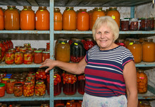 Woman Is Standing Near Shelving With Home-canned Provisions.