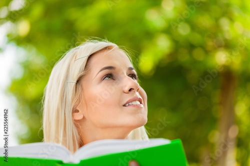 Portrait Of A Young Woman Holding A Book In A Park And
