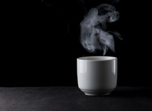 White Cup Of Coffee With Steam Over Dark Background