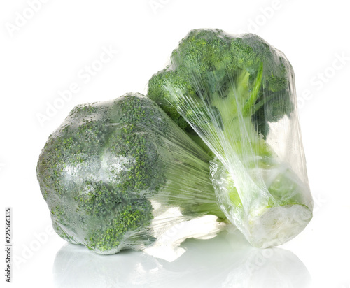 Fresh broccoli wrapped in clear plastic wrap isolated on white background