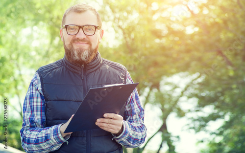 Male ecologist takes notes on the background of green plants. Tablou Canvas