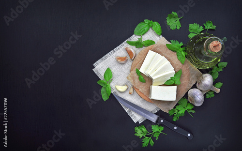 Cheese, greens and spices on a dark background. Food background. The concept of a healthy diet and lifestyle.