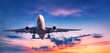 Landing airplane against colorful sky at sunset. Landscape with aircraft is flying in the blue sky with orange and pink clouds. Travel background with passenger plane. Commercial airplane. Private jet