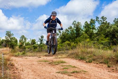 Male cyclist on ebike jumping over bump on dirt track Canvas Print
