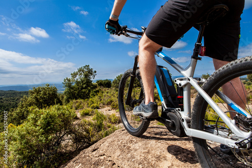 Photo  Close up of cyclist on ebike from the lower rear left, landscape and mountains i