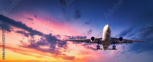 Türaufkleber Flugzeug Landing airplane against colorful sky at sunset. Landscape with aircraft is flying in the blue sky with orange and pink clouds. Travel background with passenger plane. Commercial airplane. Private jet