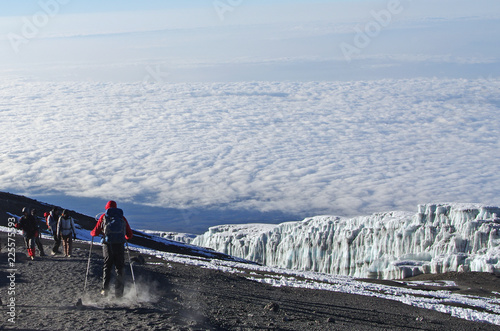 Fototapeta People walk at the top of the kilimanjaro in Tanzania above the clouds
