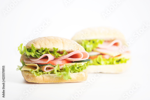 Two sandwiches on a white background. At the heart of the mini ciabatta sandwich. A filling of slices of ham, cheese, lettuce, fresh cucumbers and tomatoes. Close-up.