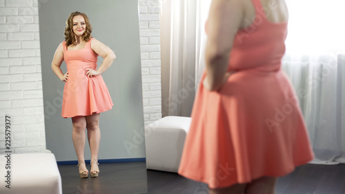 Fotografía  Cheerful overweight young lady smiling at her reflection, body positivity