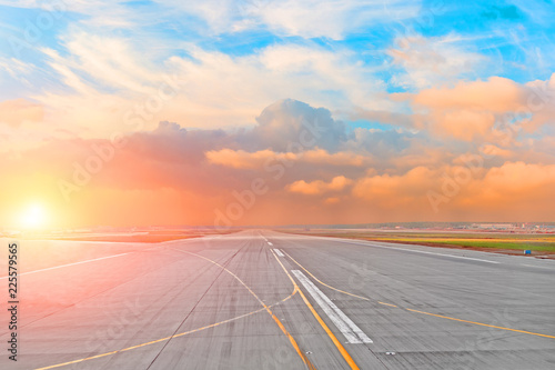 Sunset and cumulus clouds on the road runway in the airport.