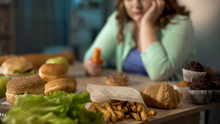 Depressed Fat Lady Sitting At Table Full Of Unhealthy Junk Food, Overeating
