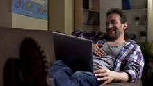 Lazy Grubby Male Lying On Couch, Looking At Laptop Laughing At Show On Screen