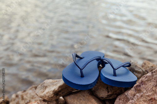 Closeup Of Blue Flip Flops On Rocky Beach At Summer Time