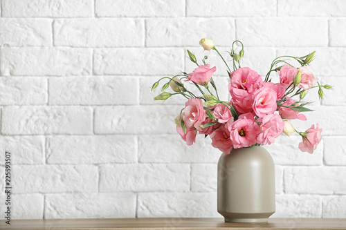 obraz PCV Vase with beautiful flowers on table against brick wall, space for text
