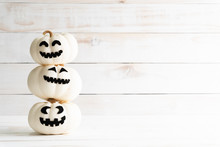 Stack Of White Ghost Pumpkin On White Wooden Background. Halloween Concept.