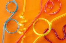 Minimalist Image Of Colorful Plastic Drinking Straws On A Orange Background