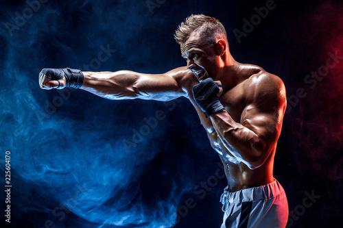 Fotografie, Tablou Studio portrait of fighting muscular man in smoke on dark background