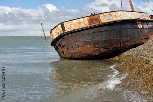 Foto op Canvas Schipbreuk primer plano de bote encallado en la playa con mástil de bote hundido