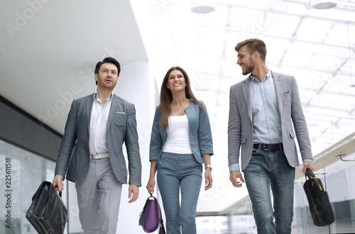 Vászonkép  smiling staff walking in the business center.
