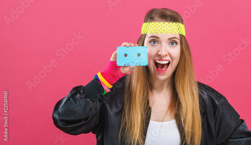 Woman in 1980's fashion holding a cassette tape on a pink background Fototapete