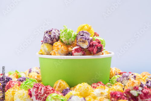 a bucket of multi-colored popcorn stands in a pile of cereal, on a white background