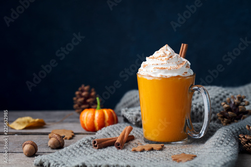 Pumpkin latte with spices. Boozy cocktail with whipped cream on top on a wooden background. Copy space.