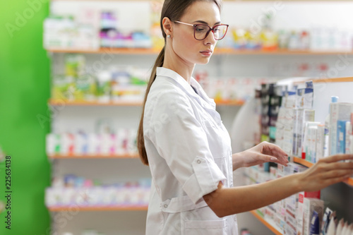 Fotobehang Apotheek A cute slim girl with dark hair and glasses,wearing a lab coat,stands next to the shelf in a pharmacy and carefully examines it.