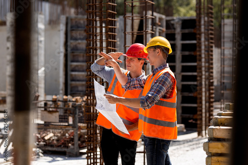 Structural engineer and construction manager in orange work vests and hard helmets explore construction documentation on the building site near the steel frames