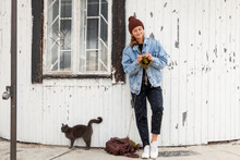 Portrait Young  Woman  In Stylish Clothes Knitting  Green  Natural Wool Hat, Next To A Cat Walks With Her Kittens  Against The Background Of The Old Lighthouse  In Sunny Autumn Day .