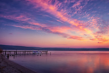 Beautiful And Calm Sunset/sunrise On A Lake With Pier And Boat.