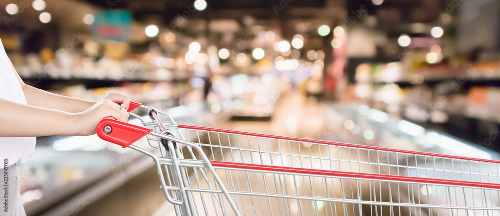 Fototapeta Woman hand hold empty red shopping cart with abstract blur supermarket discount store aisle interior defocused background with bokeh light