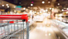 Empty Red Shopping Cart With Abstract Blur Supermarket Discount Store Aisle And Product Shelves Interior Defocused Background