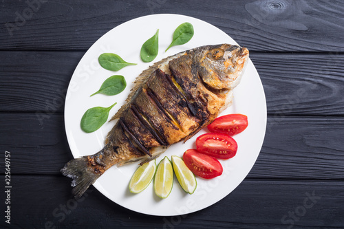 Fried fish dorado with lime , tomatoes and spinach