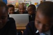 Male teacher using laptop with students in the classroom