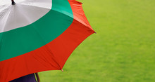 Bulgaria Flag Umbrella. Close Up Of Printed Umbrella Over Green Grass Lawn / Field. Rainy Weather Forecast Concept.