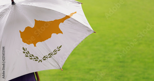 Cyprus flag umbrella. Close up of printed umbrella over green grass lawn / field. Rainy weather forecast concept.