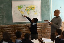 Schoolboy Explaining About World Map In Classroom