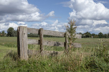 Small Old Wooden Planks, Hash Fence In A Meadow With Weeds And A Blue Cloudy Sky.