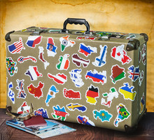 Retro Suitcase With Stickers On The Floor Against An Old Wall