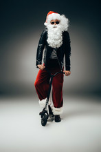 Serious Santa Claus In Sunglasses And Leather Jacket Standing With Kick Scooter On Grey Background