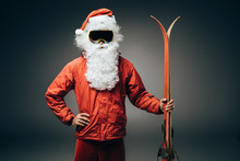 Confident Santa Claus In Ski Mask And Windbreaker Standing With Hand On Waist And Holding Skis Isolated On Grey Background