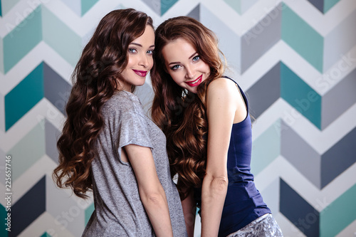 Beautiful young brunette twins women with long curly hair and evening makeup, fa Canvas Print