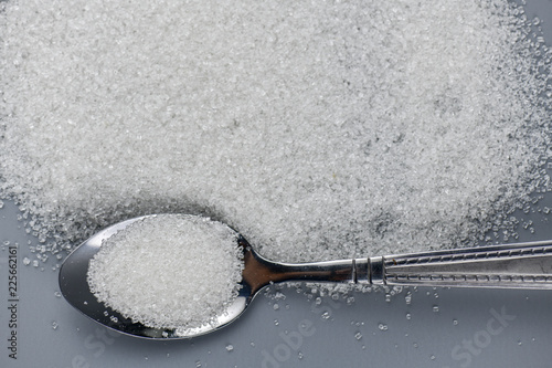 Fotografie, Obraz  A spoonful of granulated sugar on gray background