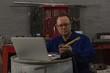 Male mechanic using laptop
